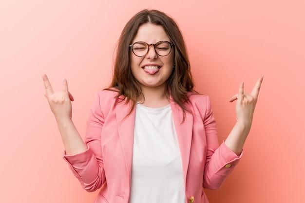 Femme caucasienne de taille plus jeune entreprise montrant le geste de la roche avec les doigts Photo Premium