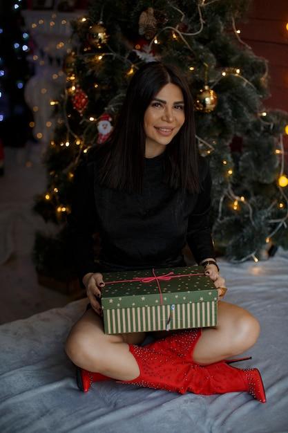 Femme Célèbre Le Nouvel An Devant L'arbre De Noël Et S'assoit Avec Le Cadeau à Portée De Main Photo Premium