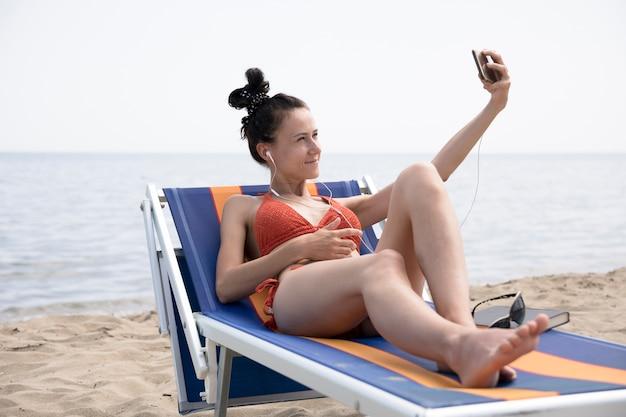 Femme sur une chaise de plage prenant un selfie Photo gratuit