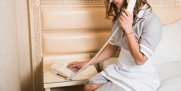 Femme de chambre assise sur un lit faisant un appel sur le téléphone de l'hôtel Photo gratuit