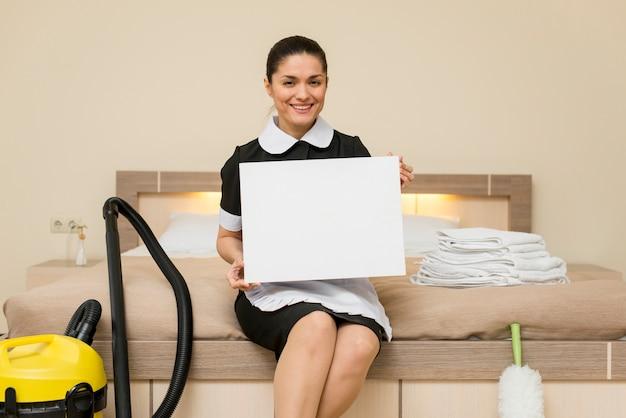 Femme de chambre dans chambre d'hôtel avec ordinateur portable Photo gratuit