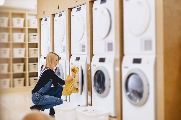 Une femme charge les draps dans le linge pour les laver et les sécher Photo Premium