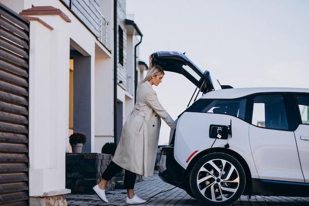Femme chargeant une voiture électro par sa maison Photo gratuit