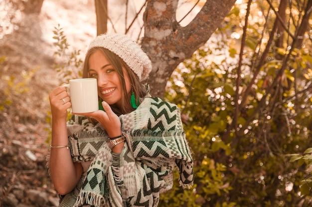 Femme charmante avec une tasse en forêt Photo gratuit