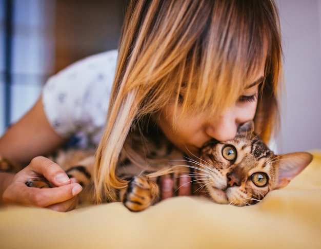 Femme et chat bengal allongé sur le lit Photo gratuit