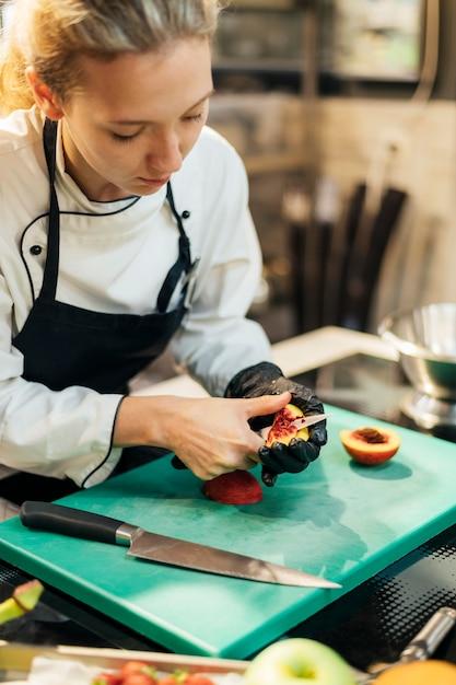 Femme Chef Couper Des Fruits Dans La Cuisine Photo Premium