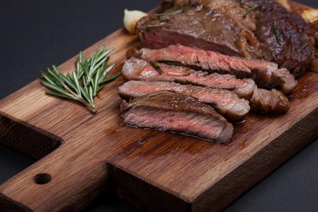 La femme chef prépare un steak de bœuf. Photo Premium