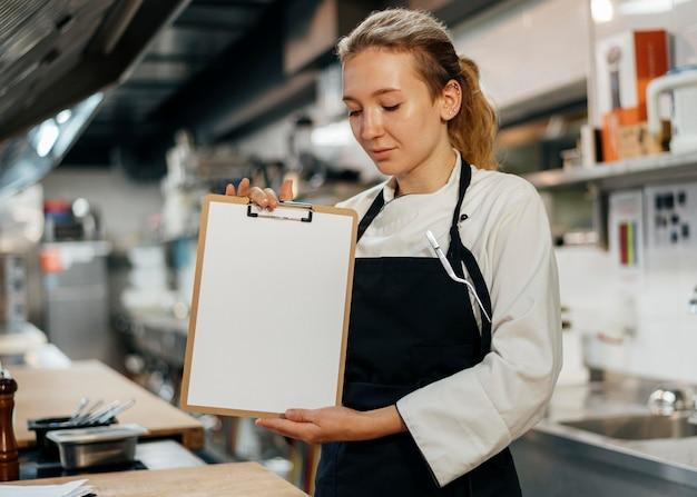 Femme Chef Tenant Le Presse-papiers Dans La Cuisine Photo Premium