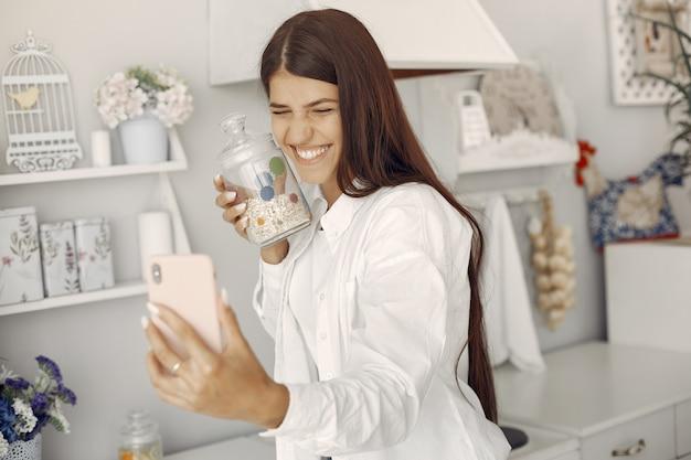 Femme, chemise blanche, debout, rhe, cuisine, selfie Photo gratuit