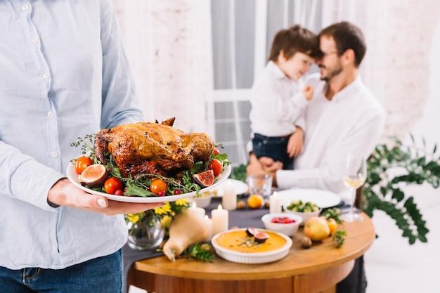 Femme en chemise debout avec du poulet cuit au four Photo gratuit