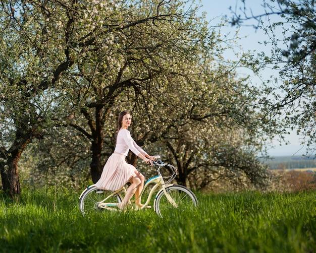 Femme chevauchant un vélo blanc rétro dans le jardin de printemps à la journée ensoleillée Photo Premium