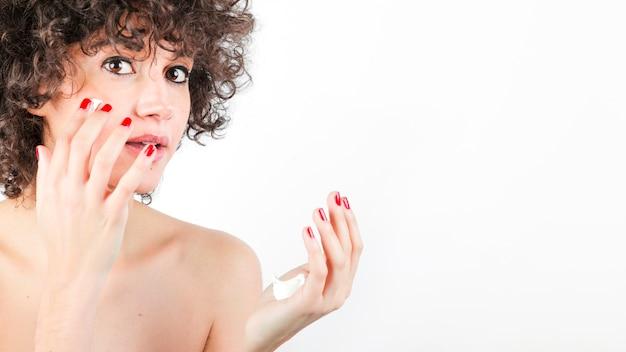 Femme, à, cheveux bouclés, appliquer, crème, à, elle, visage, contre, blanc, fond Photo gratuit
