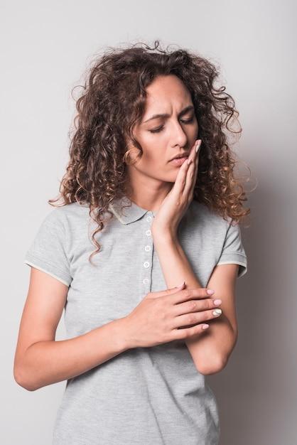 Femme, à, cheveux bouclés, avoir mal aux dents, sur fond gris Photo gratuit