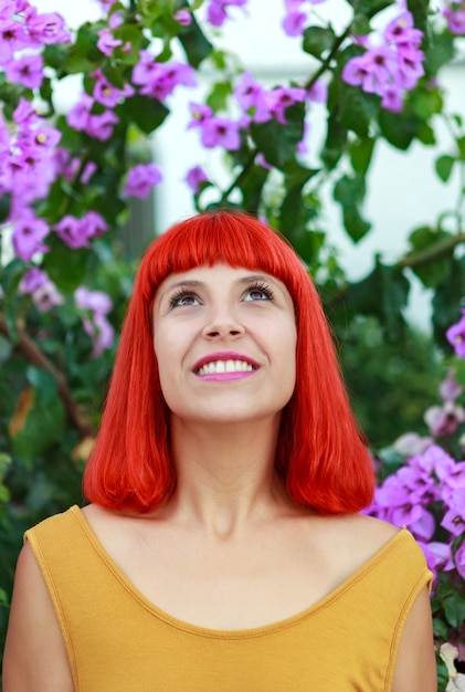Femme cheveux roux avec de belles fleurs de fond Photo Premium