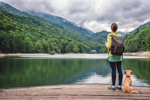 Femme Avec Un Chien Debout Sur La Jetée Au Bord Du Lac Photo Premium