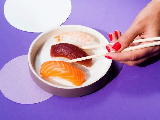 Femme choisissant un sushi au thon dans un bol blanc Photo gratuit