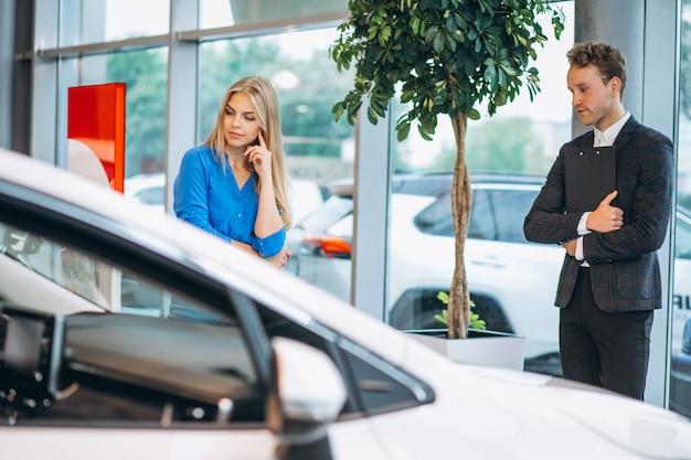 Femme choisissant une voiture dans une salle d'exposition Photo gratuit