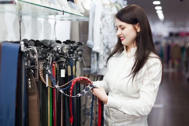 Femme choisit la ceinture au magasin Photo gratuit