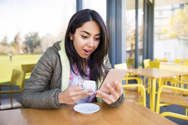 Femme choquée à l'aide de smartphone et de boire du café au café Photo gratuit
