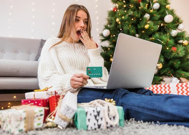 Femme choquée, shopping en ligne à l'arbre de noël Photo gratuit