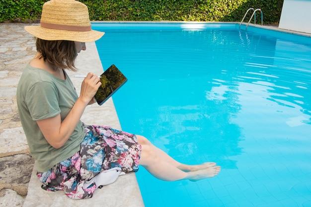 Femme Ciblée, Dans, Chapeau Paille, Séance, à, Poolside Photo gratuit