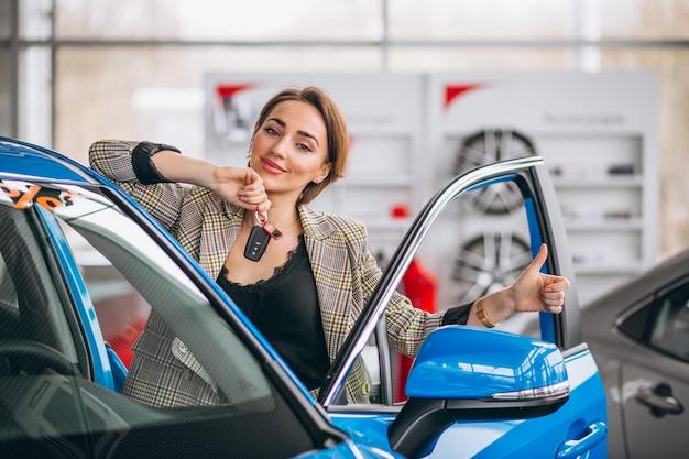 Femme avec des clés près de la voiture Photo gratuit