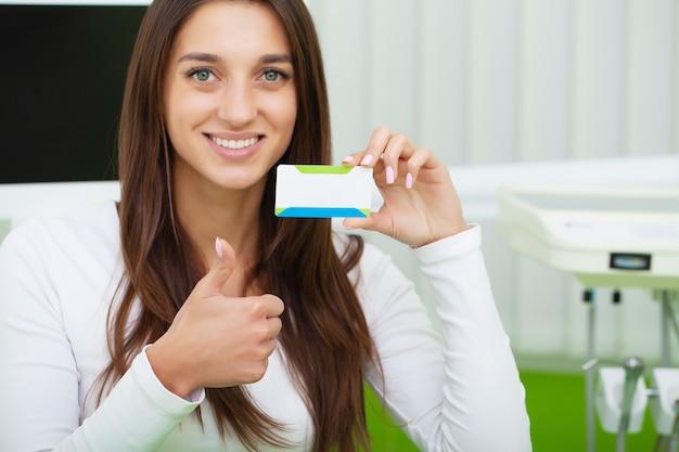 Femme à La Clinique Dentaire Détenant Une Carte De Visite Vierge Photo Premium