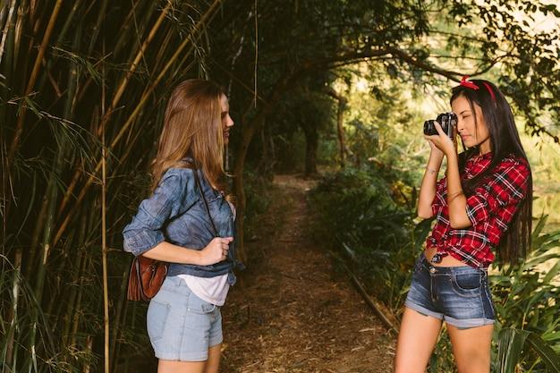 Femme en cliquant sur la photo de son ami avec caméra en forêt Photo gratuit