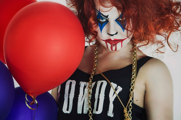 Femme, clown aux cheveux roux avec un ballon, halloween Photo Premium