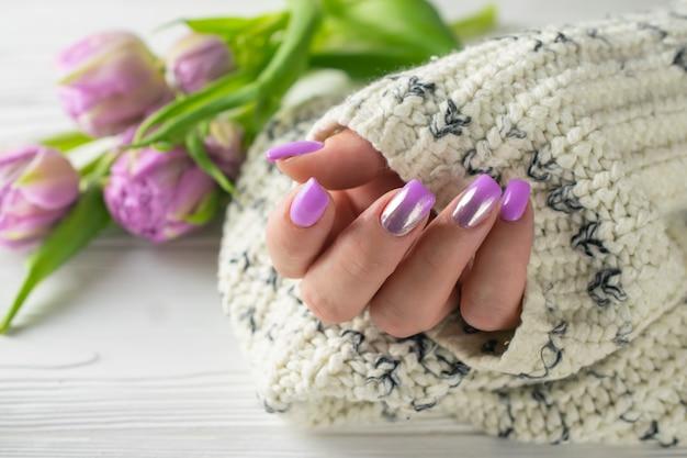 Femme coiffée avec du vernis à ongles violet, manucure, soin des mains Photo Premium