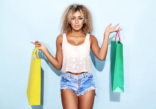 Femme Avec Une Coiffure Afro Blonde Après Le Shopping Photo gratuit