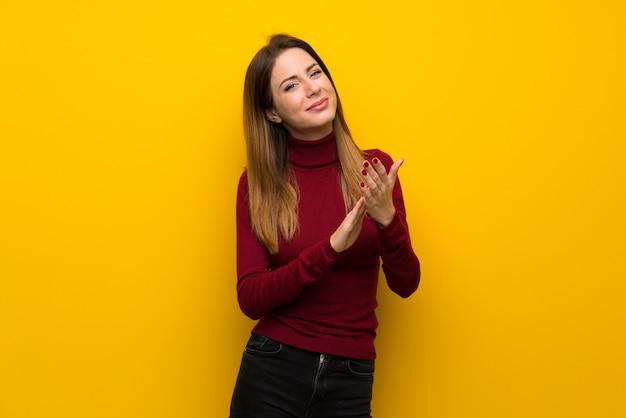 Femme, à, col roulé, sur, jaune, mur, applaudir, après, présentation, dans, a, conférence Photo Premium