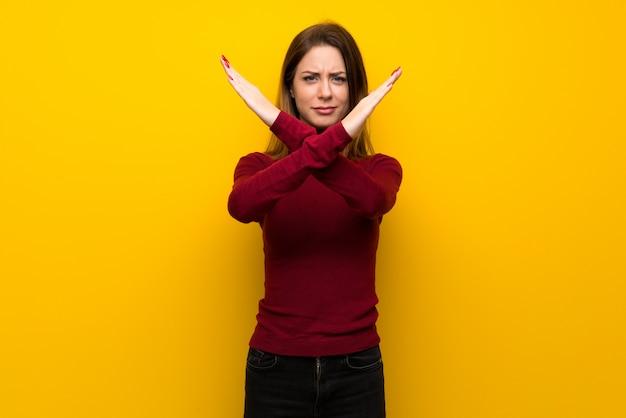 Femme, à, col roulé, sur, mur jaune, aucun geste Photo Premium