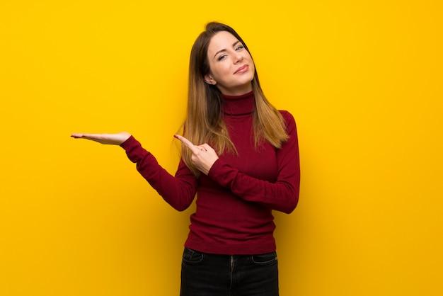 Femme avec col roulé sur un mur jaune tenant une surface imaginaire sur la paume pour insérer une annonce Photo Premium