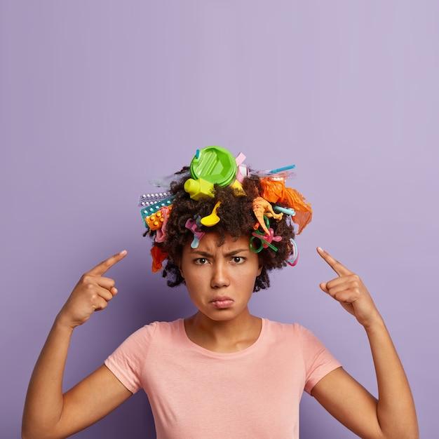 Femme En Colère Insatisfaite Posant Avec Des Ordures Dans Ses Cheveux Photo gratuit