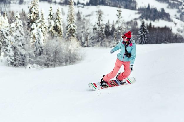 Femme en combinaison de ski regarde par-dessus son épaule en descendant la colline sur son snowboard Photo gratuit