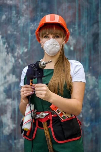 Femme En Combinaison Verte Et Masque De Protection Tenant La Perceuse Sur Fond Abstrait Photo Premium