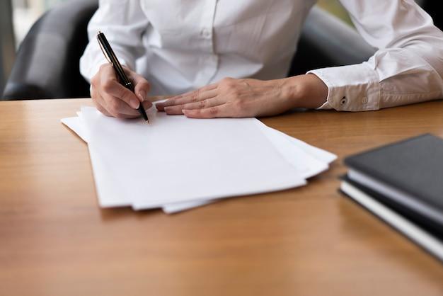 Femme concentrée, écriture, sur, papier blanc Photo gratuit