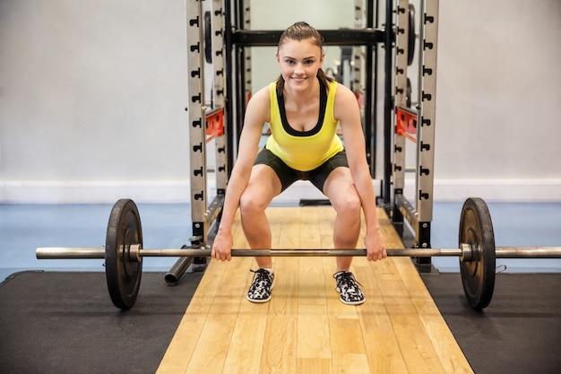 Femme concentrée sur le point de soulever une barre et des poids Photo Premium