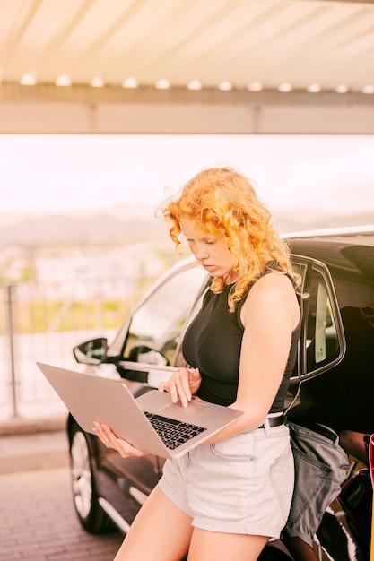 Femme concentrée travaillant sur un ordinateur portable à côté d'une voiture Photo gratuit