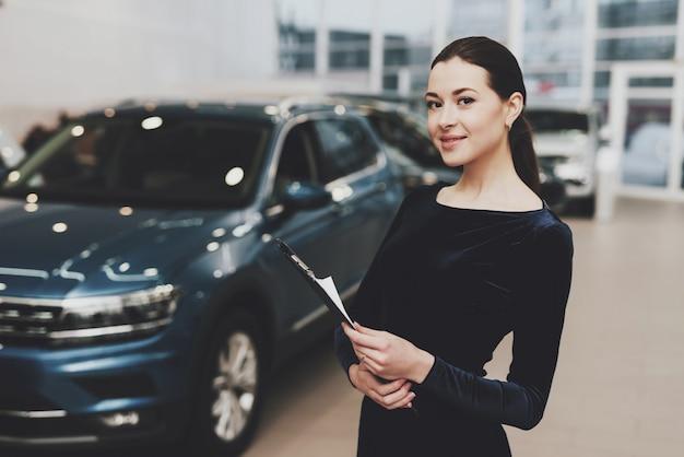 Femme concessionnaire automobile en robe noire auto salon. Photo Premium