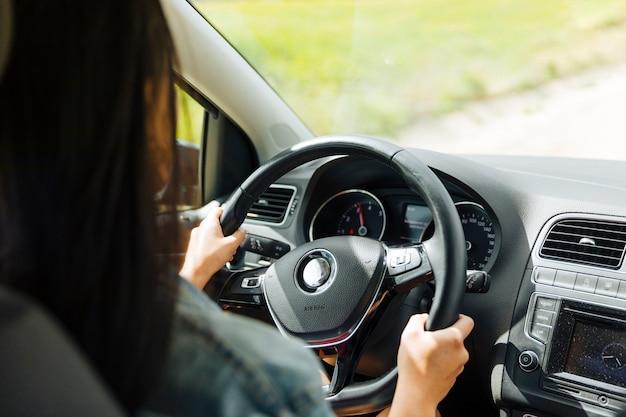 Femme conduisant une voiture en milieu rural Photo gratuit