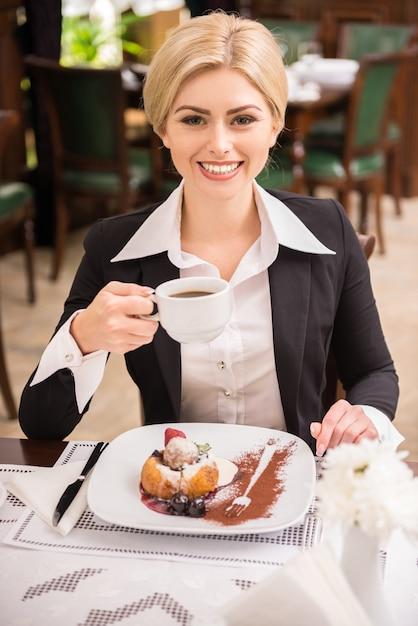 Femme confiante en costume profitant de café pour déjeuner d'affaire. Photo Premium