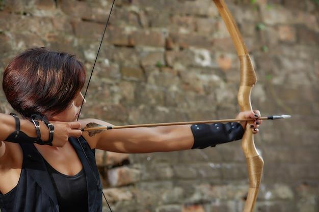 Femme Confiante Tirant De L'arc, Se Focaliser, Détourner Les Yeux. Photo Premium