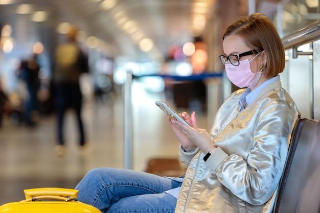 Une Femme Contrariée Par L'annulation D'un Vol, écrit Un Message à Sa Famille, Assise Dans Un Terminal D'aéroport Presque Vide En Raison D'une Pandémie De Coronavirus Photo Premium