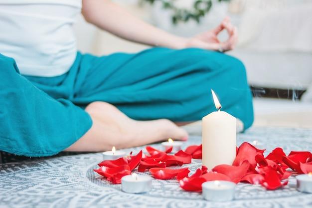 Femme en costume ethnique pratiquant le yoga devant des bougies brûlées et des pétales de rose rouges Photo Premium