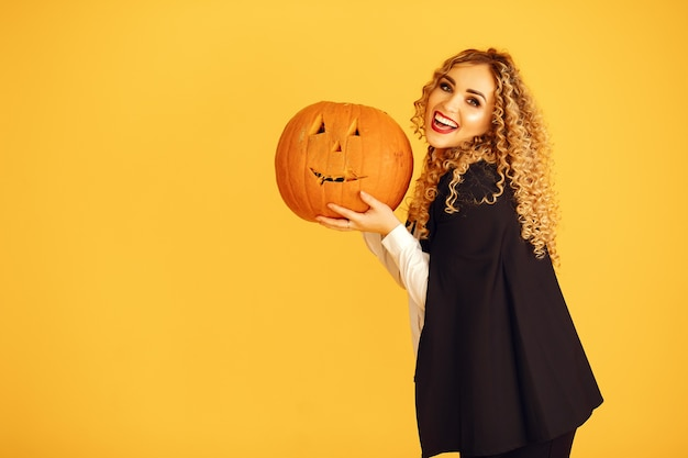 Femme En Costume Noir. Dame Avec Du Maquillage D'halloween. Fille Debout Sur Un Fond Jaune. Photo gratuit