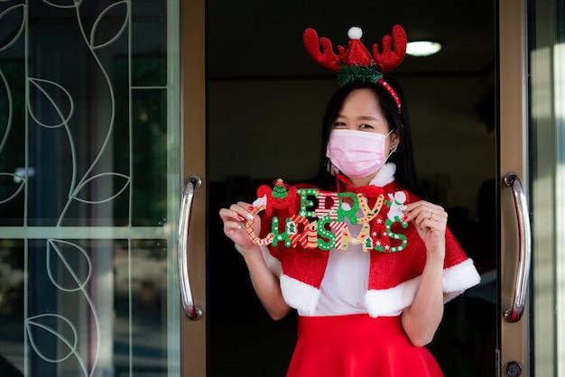 Femme En Costume De Père Noël Avec Masque Facial Le Jour De Noël Photo Premium