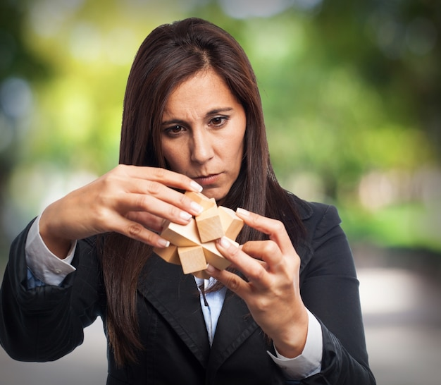 Femme avec le costume de résoudre un jeu d'intelligence en bois Photo gratuit