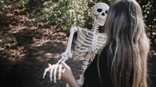 Femme En Costume De Sorcière Squelette Penché Photo gratuit